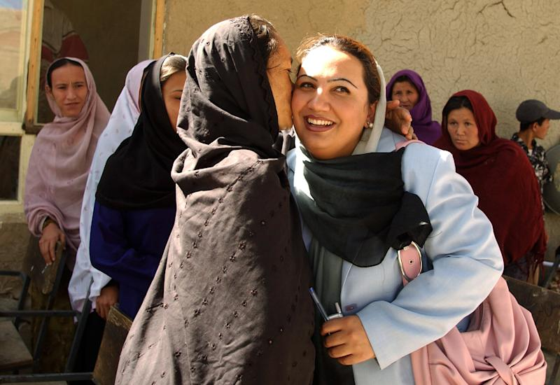 File photo of Afghan lawmaker Shukria Barekzai (C-R) being hugged by supporters during a campaign meeting in Kabul in 2005 (AFP Photo/Farzana Wahidy)