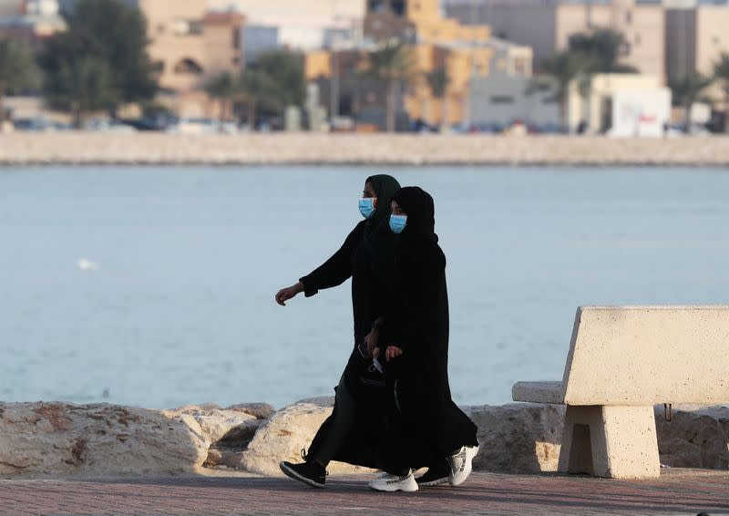 Women wear protective face masks, as they walk, after Saudi Arabia imposed a temporary lockdown on the province of Qatif, following the spread of coronavirus, in Qatif