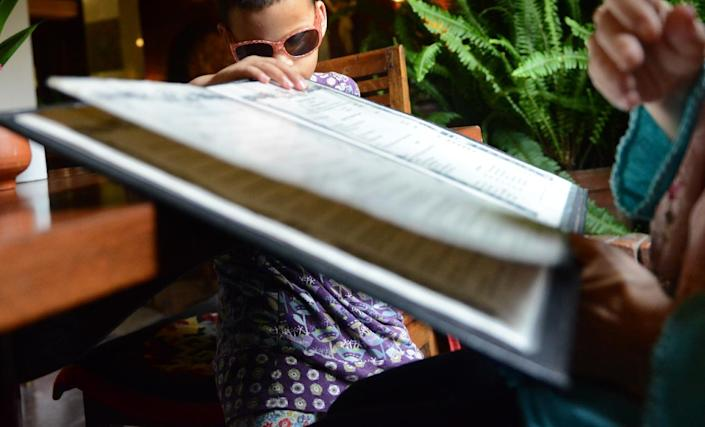 Seven-year-old blind girl who goes under the pseudonym Anna (L) at a restaurant with her adoptive mother in Kathmandu on July 23, 2014 (AFP Photo/Prakash Mathema)