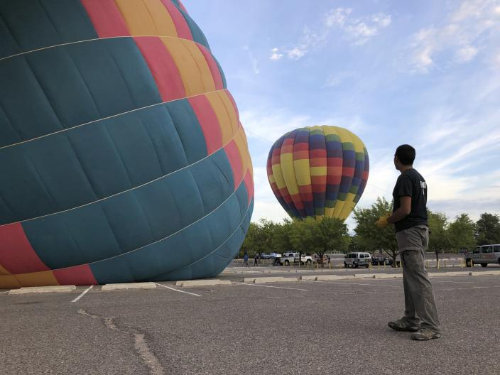 Elijah Sanchez monitors the inflation of hot air balloons operated by Rainbow Ryders in Albuquerque, N.M., on Tuesday, Oct. 1, 2019. Sanchez, 20, will be among the youngest pilots to launch as part of this year's Albuquerque International Balloon Fiesta. The nine-day event is expected to draw several hundred thousand spectators and hundreds of balloonists from around the world. It will kick off Oct. 5 with a mass ascension. (AP Photo/Susan Montoya Bryan)