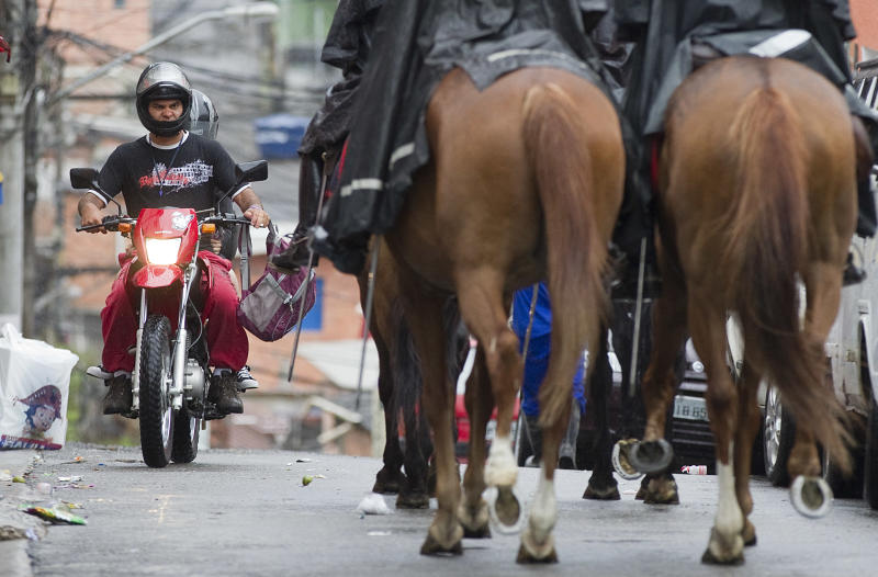 A motorcyclist drives along a road where mounted military police patrol the Paraisopolis slum in Sao Paulo, Brazil, early Tuesday, Nov. 13, 2012. At least 140 people have been murdered in South America's biggest city over the past two weeks in a rising wave of violence, Sao Paulo's Public Safety Department said on Sunday. (AP Photo/Andre Penner)