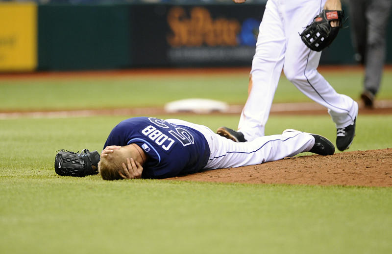 Tampa Bay Rays starting pitcher Alex Cobb grabs his head and lies on the pitcher's mound after being hit by a line drive by Kansas City Royals' Eric Hosmer during the fifth inning of a baseball game Saturday, June 15, 2013, in St. Petersburg, Fla. Cobb was taken off the field on a stretcher. (AP Photo/Brian Blanco)