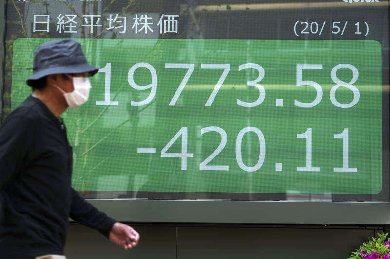 A man walks past an electronic stock board showing Japan's Nikkei 225 index at a securities firm in Tokyo Friday, May 1, 2020. Shares have dropped in Asia after Wall Street ended its best month in 33 years with losses on fresh news of economic carnage from the coronavirus pandemic. (AP Photo/Eugene Hoshiko)