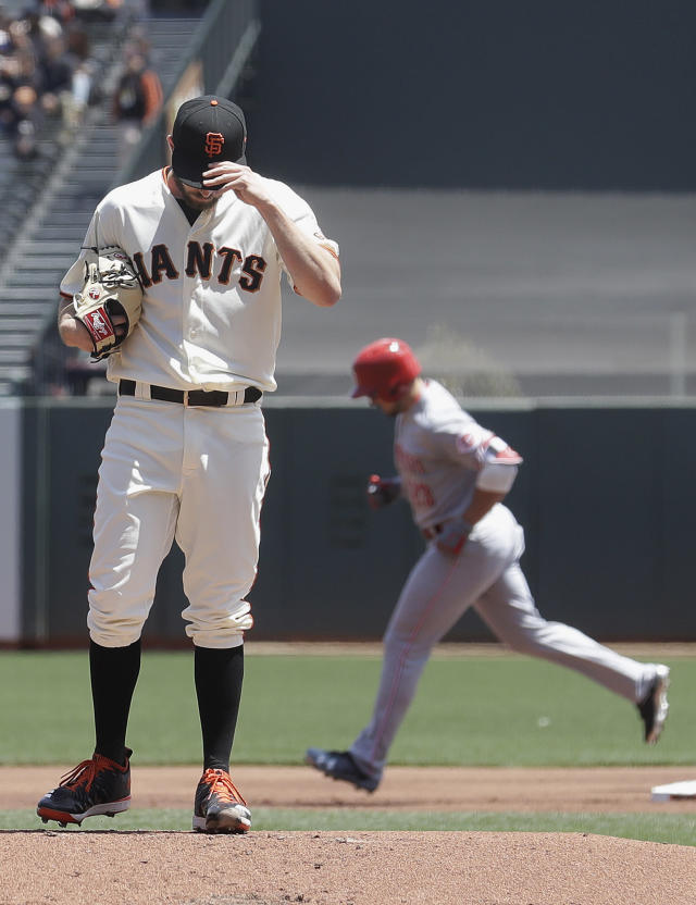 Cincinnati Reds' Adam Duvall, rear, rounds the bases after hitting a three-run home run off of San Francisco Giants pitcher Andrew Suarez, foreground, during the first inning of a baseball game in San Francisco, Wednesday, May 16, 2018. (AP Photo/Jeff Chiu)
