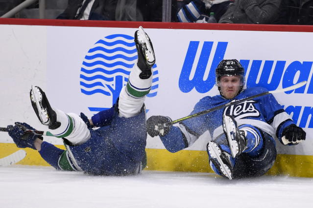 Winnipeg Jets' Nikolaj Ehlers (27) and Vancouver Canucks' Troy Stecher (51) fall to the ice after colliding during the second period of an NHL hockey game Tuesday, Jan. 14, 2020, in Winnipeg, Manitoba. (Fred Greenslade/The Canadian Press via AP)