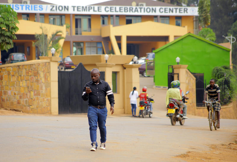 In this photo taken Friday Sept. 6, 2019, Albert Nabonibo, a well-known gospel singer in Rwanda, walks out from the Church of Zion temple celebration centre in Kigali, Rwanda. Nabonibo shocked many last month when he revealed he is a gay man in a country where such a public assertion of homosexuality is unheard of. (AP Photo/Olivier Muhizi)