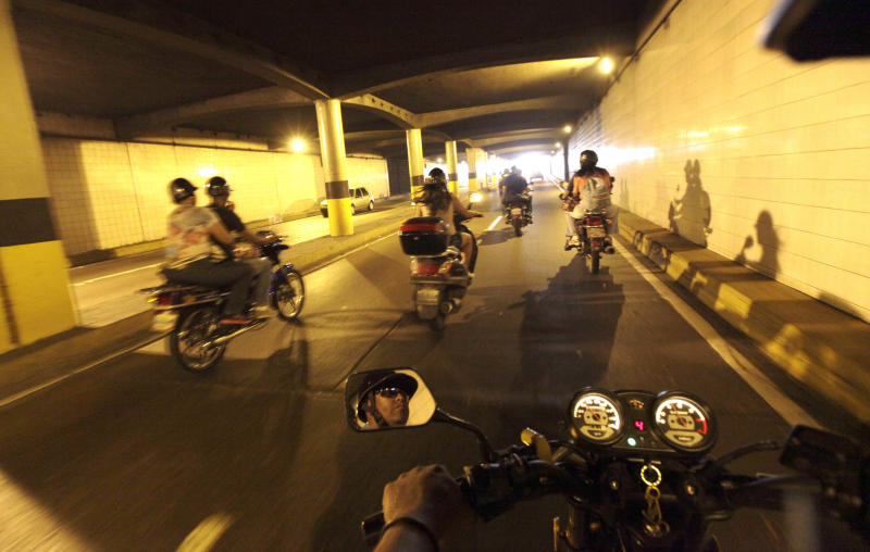 Mototaxi driver, Fidel Suarez, reflected in his rearview mirror, rides through a highway tunnel in Caracas, Venezuela, Thursday, July 4, 2013. Mototaxis, once essentially unheard of in this South American country, await customers on every other street corner in the downtown business district. At rush hour everyone from working-class laborers to lawyers in business suits can be seen hopping on the back of motorcycles. (AP Photo/Ariana Cubillos)