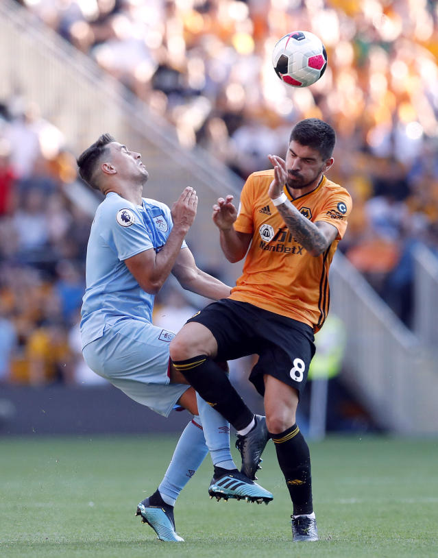Wolverhampton Wanderers's Ruben Neves, right, and Burnley's Matthew Lowton battle for the ball during the English Premier League soccer match Between Burnley and Wolverhampton Wanderers at Molineux, Wolverhampton, England, Sunday Aug. 25, 2019. (Darren Staples/PA via AP)