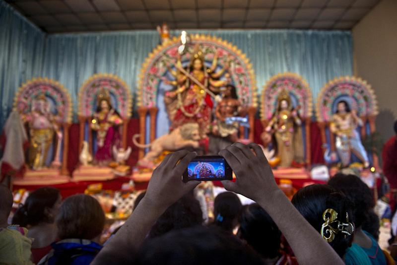 A Bangladeshi Hindu devotee takes photographs with his cell phone of the Durga pandal at the Dhakeshwari temple in Dhaka on October 2, 2014 (AFP Photo/Munir Uz Zaman)