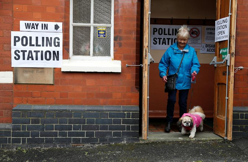A voter leaves the polling station with her dog on general election day in Congleton, Britain, June 8, 2017. REUTERS/Paul Childs