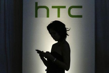 A guest checks her mobile as she arrives for the launch of new HTC products in New York