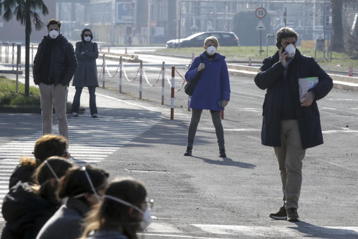 Workers wear masks at the Unilever factory where a 38-year-old working in the research and development branch fall ill with the new virus from China, in Casalpusterlengo, Northern Italy, Saturday, Feb. 22, 2020. A dozen northern Italian towns were on effective lockdown Saturday after the new virus linked to China claimed two fatalities in Italy and sickened an increasing number of people who had no direct links to the origin of the virus. (AP Photo/Luca Bruno)