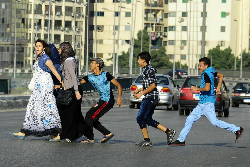FILE - In this Aug. 20, 2012 file photo, an Egyptian youth, trailed by his friends, gropes a woman crossing the street with her friends in Cairo, Egypt. A video posted on Facebook Aug. 15, 2018, by an Egyptian woman who says a man stalked her at a bus stop has stirred online debate, with many -- including women -- taking the man's side. Some say he was politely flirting and the woman overreacted, while others have speculated about what she was wearing, suggesting she was the one at fault. The diverging responses point to the difficulty in combatting the rampant sexual harassment on Egypt's streets. (AP Photo/Ahmed Abd El Latif, El Shorouk Newspaper, File)