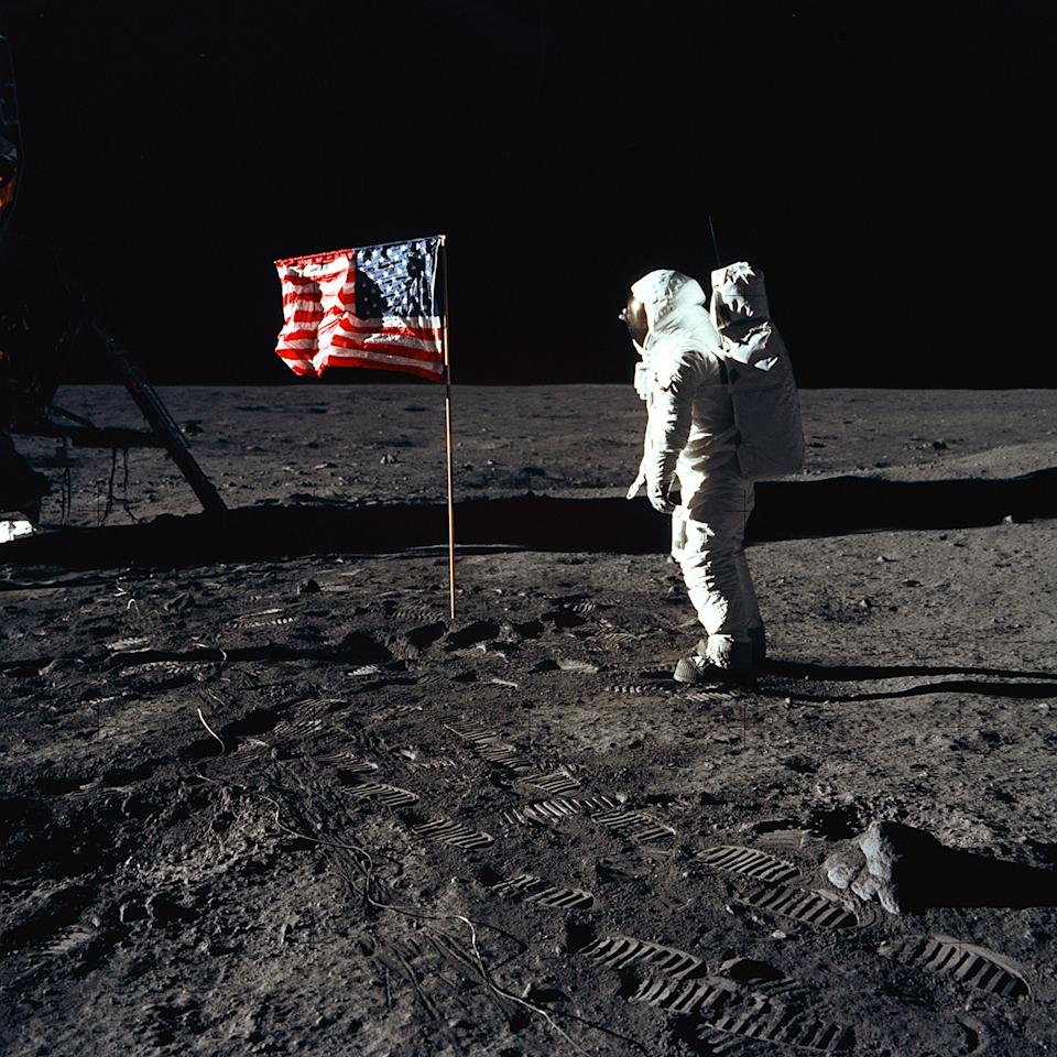 """Astronaut Buzz Aldrin, lunar module pilot of the first lunar landing mission, poses for a photograph beside the deployed United States flag during an Apollo 11 Extravehicular Activity (EVA) on the lunar surface on July 20, 1969. The Lunar Module (LM) is on the left, and the footprints of the astronauts are clearly visible in the soil of the Moon. Astronaut Neil A. Armstrong, commander, took this picture with a 70mm Hasselblad lunar surface camera. While astronauts Armstrong and Aldrin descended in the LM, the """"Eagle"""", to explore the Sea of Tranquility region of the Moon, astronaut Michael Collins, command module pilot, remained with the Command and Service Modules (CSM) """"Columbia"""" in lunar-orbit. (Photo: NASA)"""