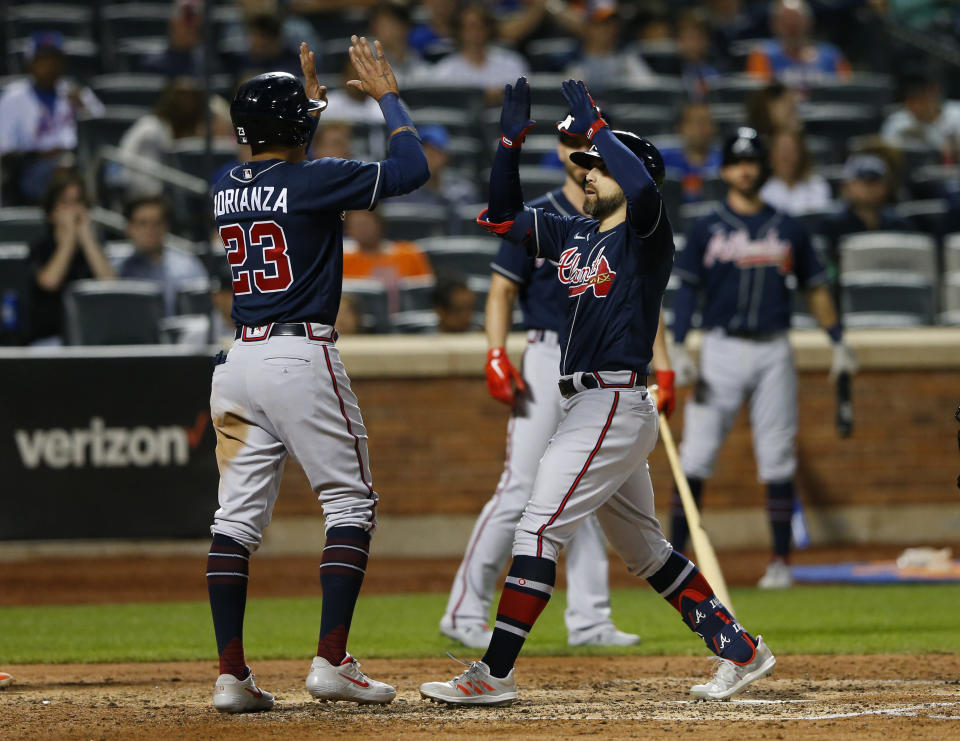 Atlanta Braves center fielder Ender Inciarte (11) and third baseman Ehire Adrianza (23) celebrate after scoring during fifth the inning of a baseball game Wednesday, June 23, 2021, in New York. (AP Photo/Noah K. Murray)