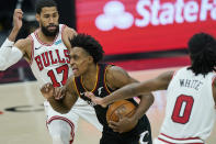 Cleveland Cavaliers' Collin Sexton, center, drives between Chicago Bulls' Garrett Temple, left, and Coby White during the second half of an NBA basketball game Wednesday, April 21, 2021, in Cleveland. (AP Photo/Tony Dejak)
