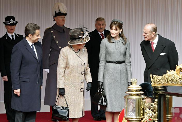 <p>As a former fashion model, Carla Bruni (who's also the wife of former French president, Nicolas Sarkozy) knows how to dress for royalty. She wore a grey belted coat dress and matching pillbox hat when she visited London in 2008. </p>