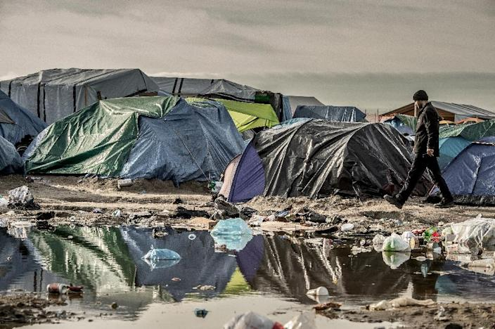 """A man walks past tents on November 5, 2015 in the """"Jungle"""" migrant camp in Calais, northern France (AFP Photo/Philippe Huguen)"""