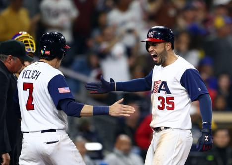 Christian Yelich (left) greets Eric Hosmer after the latter's go-ahead two-run homer against Venezuela. (Getty Images)