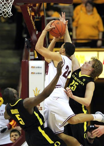 Oregon's Olu Ashaolu (5) takes a charge against Arizona State's Trent Lockett as Oregon's E.J. Singler (25) defends during the first half of an NCAA college basketball game, Thursday, Jan. 12, 2012, in Tempe, Ariz. (AP Photo/Ross D. Franklin)