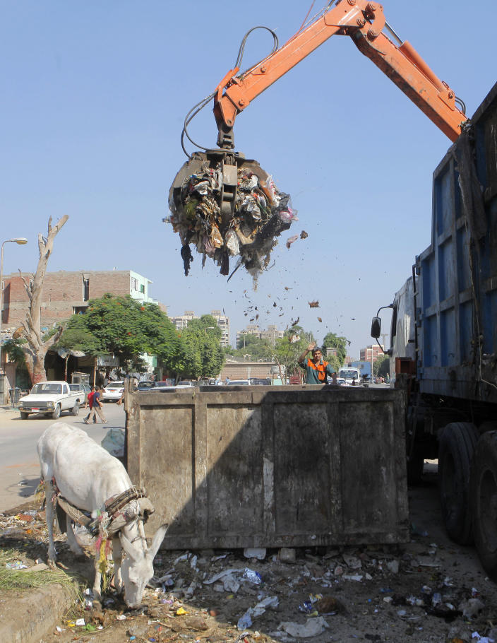In this Thursday, Aug. 16, 2012 photo, a waste collector unloads garbage from a container in Cairo. A government modernization effort flopped. A swine flu panic prompted the mass slaughter of the pigs that recycled Cairo's organic garbage; the city's metal trash bins were easy prey for thieves, especially during the global scrap metal boom. Now the garbage crisis in the Arab world's biggest city is posing a significant test for the newly elected government that replaced longtime autocratic leaders. (AP Photo)