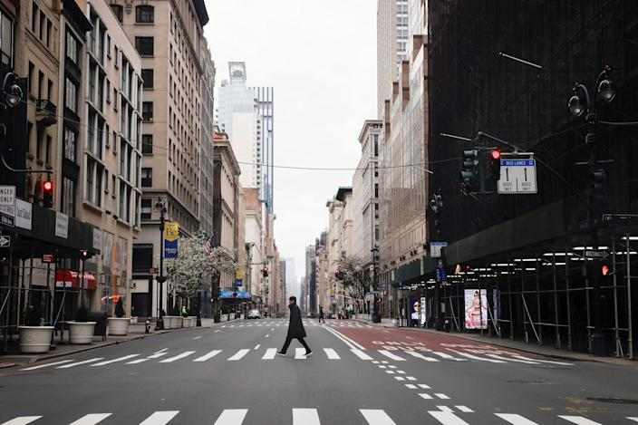 A man crosses a nearly empty 5th Avenue in midtown Manhattan during the outbreak of the coronavirus disease (COVID-19) in New York City, New York, U.S., March 25, 2020.