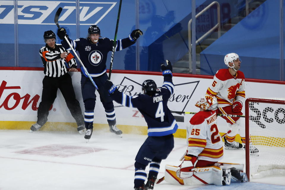 Winnipeg Jets' Patrik Laine (29) celebrates his overtime goal with Neal Pionk (4), as Calgary Flames goaltender Jacob Markstrom (25) and Flames' Mark Giordano (5) react during an NHL hockey game Thursday, Jan. 14, 2021, in Winnipeg, Manitoba. (John Woods/The Canadian Press via AP)