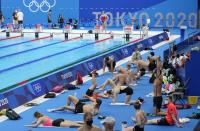 FILE - In this July 22, 2021, file photo, Germany's team exercises during a swimming training session at the Tokyo Aquatics Centre at the 2020 Summer Olympics in Tokyo. With hundreds of swimmers scrambling to get their warmup done at the same time, multiple athletes in each lane, everyone diving over one another and some competitors using snorkels, kickboards and other paraphernalia, warmup is organized chaos. (AP Photo/Martin Meissner, File)