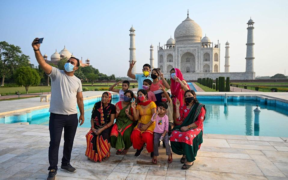 A group of tourists pose with the world-famous mausoleum - AFP