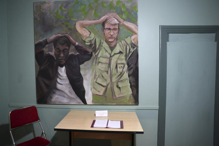 In this Sept. 26, 2019, photo, a painting of one of the images of the takeover of U.S. Embassy in Tehran in 1979 which shows U.S. Marine Sgt. Ladell Maples of Earle, Ark., left, and Cpl. Steve Kirtley of Little Rock, Ark., with their hands above their heads adorns a wall of the embassy, now partly a museum, in Tehran, Iran. Images like those of surrendering American troops carry a strong resonance for hard-liners in Iran. (AP Photo/Vahid Salemi)