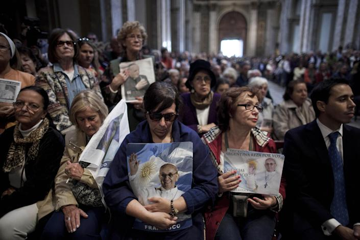 People holding images of Pope Francis attend Mass at the Metropolitan Cathedral in Buenos Aires, Argentina, Sunday, March 17, 2013. Argentine's former Cardinal Jorge Mario Bergoglio was chosen as leader of the Catholic Church on March 13, 2013. (AP Photo/Natacha Pisarenko)