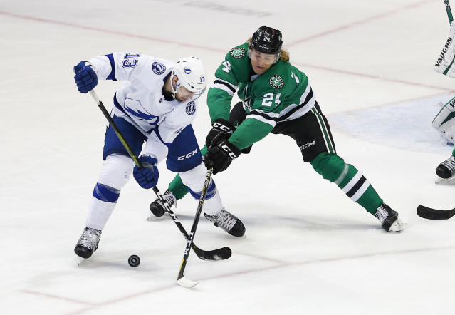 Tampa Bay Lightning forward Cedric Paquette (13) battles Dallas Stars forward Roope Hintz (24) for the puck during the first period of an NHL hockey game, Tuesday, Jan. 15, 2019, in Dallas. (AP Photo/Brandon Wade)