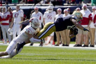 Notre Dame tight end Michael Mayer stretches out after making a catch from quarterback Jack Coan as Wisconsin safety Scott Nelson makes the tackle during the first half of an NCAA college football game Saturday, Sept. 25, 2021, in Chicago. (AP Photo/Charles Rex Arbogast)