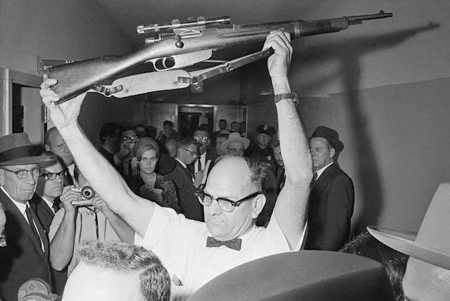 <p>A Dallas policeman holds up the rifle used to kill President John F. Kennedy at police headquarters in Dallas, Texas on Nov. 22, 1963. Lee Harvey Oswald has been charged with the murder. (Photo: Bettmann/Getty Images) </p>