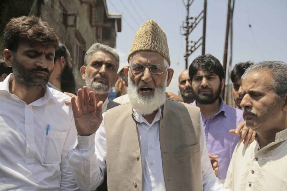 Syed Ali Shah Geelani speaks to the media as he walks outside his house to participate in a march towards the United Nations Military Observer Group office in Srinagar, Indian controlled Kashmir, Friday, July 29, 2016. Geelani, a top separatist leader and one of the severest critics of Indian rule in the disputed Himalayan region of Kashmir, died late Wednesday, Sept. 1, 2021. He was 92. (AP Photo/Mukhtar Khan)