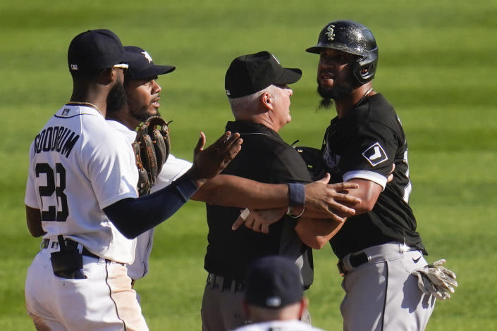 Chicago White Sox's Jose Abreu, right, is held back by second base umpire Tim Timmons from Detroit Tigers shortstop Niko Goodrum (28) as Jeimer Candelario, second from left, tries to help in the ninth inning of a baseball game in Detroit, Monday, Sept. 27, 2021. (AP Photo/Paul Sancya)