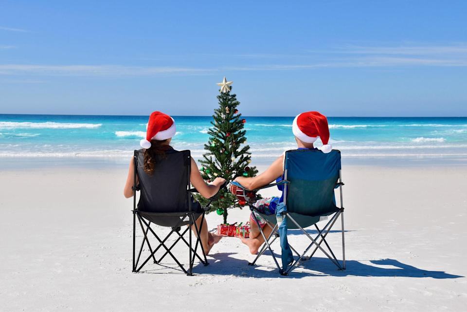 Two Australians on the beach in Christmas hats