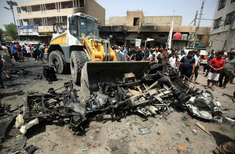A bulldozer clears the wreckage following a car bomb attack in Sadr City, a Shiite area north of the capital Baghdad, on May 11, 2016