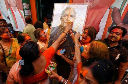 Supporters of the Bharatiya Janata Party (BJP) celebrate after learning of the initial poll results outside the party headquarters in Kolkata