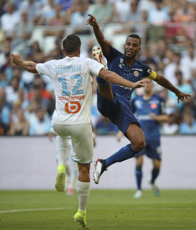 Reims' Alaixys Romao, right, challenges Marseille's Kevin Strootman during the French League One soccer match between Marseille and Reims at the Velodrome Stadium in Marseille, France, Saturday, Aug. 10, 2019. (AP Photo/Daniel Cole)