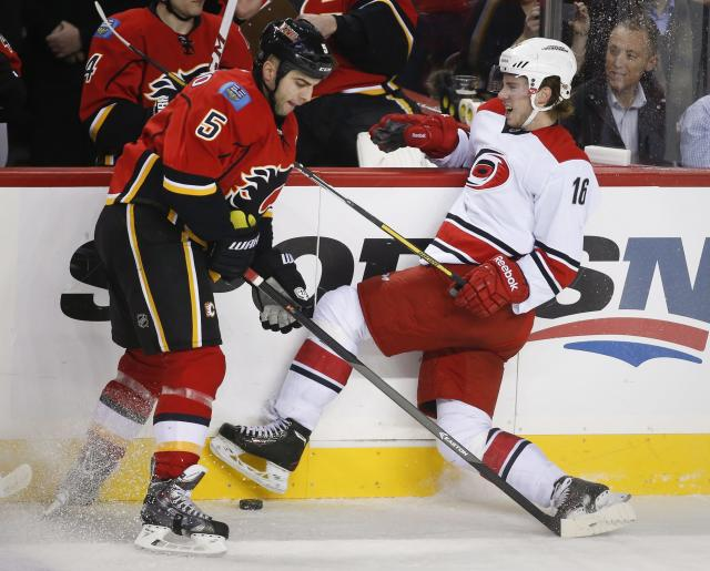 Carolina Hurricanes' Elias Lindholm, right, from Sweden, crashes into the boards as Calgary Flames' Mark Giordano digs for the puck during first period NHL hockey action in Calgary, Alberta, Thursday, Dec. 12, 2013. (AP Photo/The Canadian Press, Jeff McIntosh)