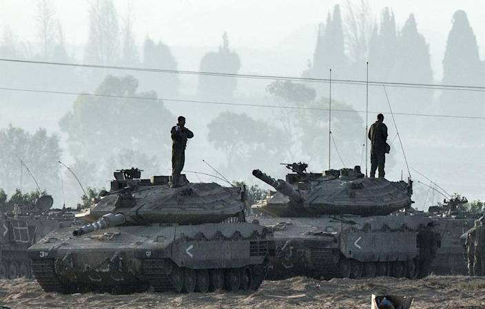 Israeli soldiers stand on Merkava tanks in an army deployment area near the border with the Gaza Strip, on July 8, 2014 (AFP Photo/Jack Guez)