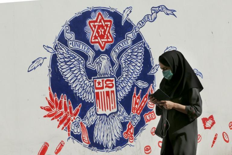 A woman walks past a mural painted on the outer walls of the former US embassy in the Iranian capital Tehran