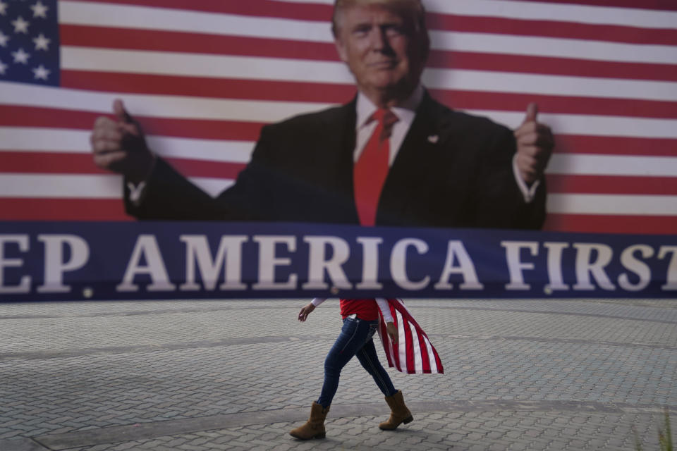 FILE - In this Jan. 6, 2021, file photo, a woman draped in an American flag walks past a banner supporting President Donald Trump during a rally in Huntington Beach, Calif. For America's allies and rivals alike, the chaos unfolding during Donald Trump's final days as president is the logical result of four years of global instability brought on by the man who promised to change the way the world viewed the United States. (AP Photo/Jae C. Hong, File)