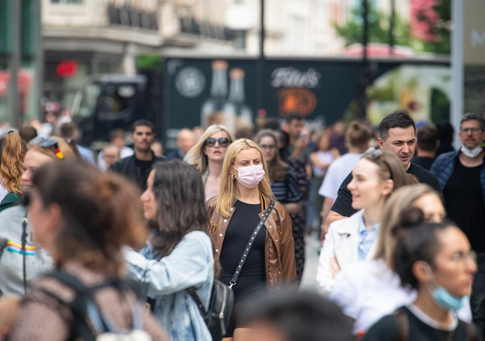 A woman wearing a face mask among a crowd of pedestrians on Oxford Street, London, as Prime Minister Boris Johnson warns that coronavirus infections will rise as he prepared to announce the lifting of restrictions from July 19. Picture date: Monday July 12, 2021.