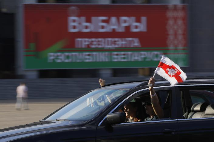 People in a car hold national flag as they take part in a flash mob ahead of presidential elections in Minsk, Belarus, Saturday, Aug. 8, 2020. On Saturday evening, police arrested at least 10 people as hundreds of opposition supporters drove through the center of the capital waving flags and brandishing clenched-fist victory signs from the vehicles' windows. The presidential election in Belarus is scheduled for August 9, 2020. (AP Photo/Sergei Grits)