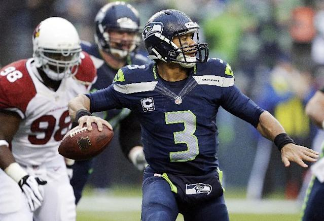 Seattle Seahawks quarterback Russell Wilson (3) passes as Arizona Cardinals defensive end Frostee Rucker (98) moves in on defense in the second half of an NFL football game, Sunday, Dec. 22, 2013, in Seattle. (AP Photo/Elaine Thompson)