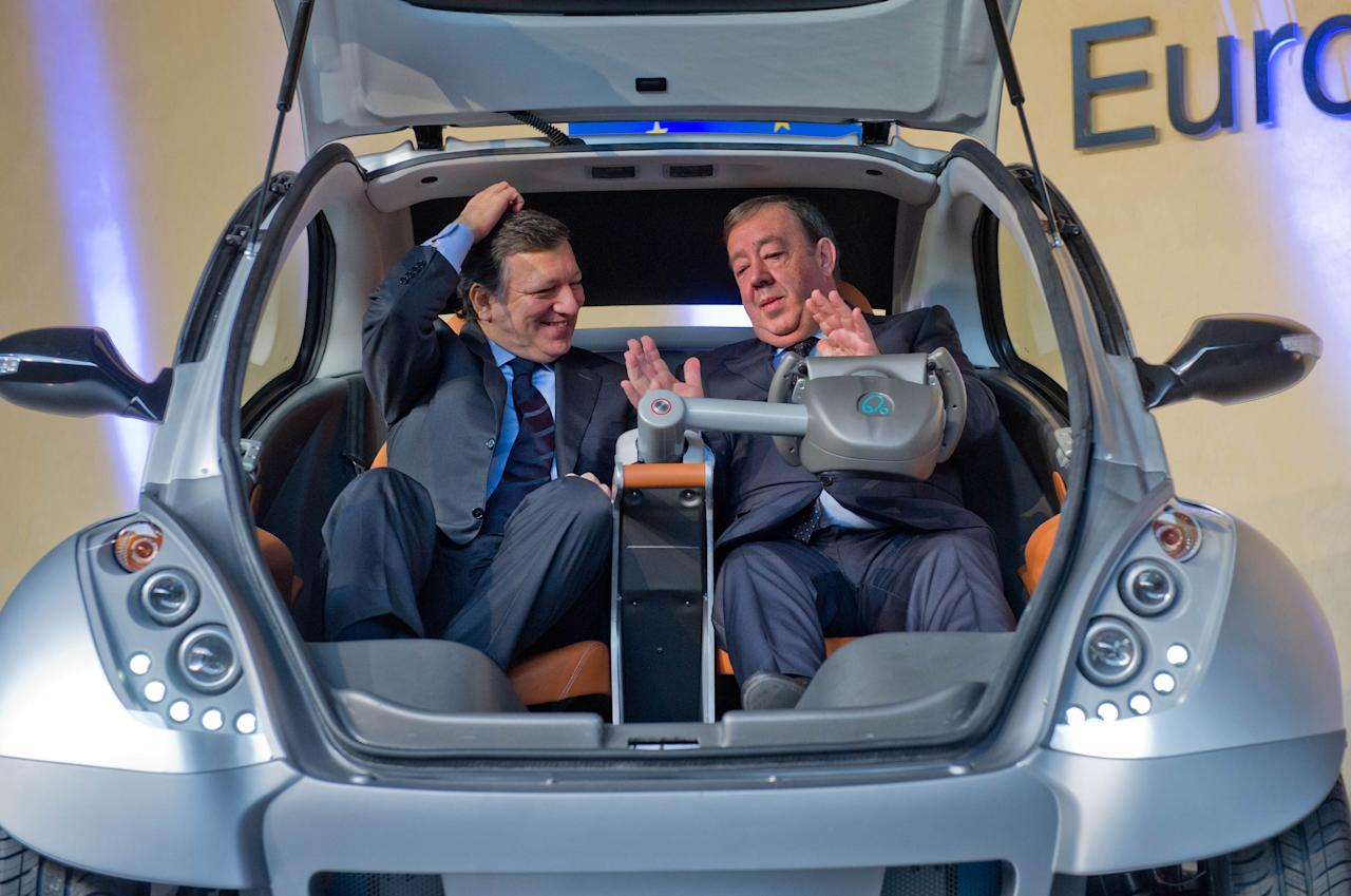 "BRUSSELS, BELGIUM - JANUARY 24:  EU Commission President Jose Manuel Barroso and Jesus Echave, chairman of the HIRIKO-AFYPAIDA corporate consortium, sit in the first prototype of the HIRIKO electric car, during the global launch of Hiriko Driving Mobility at the EU Commission headquarters on January 24, 2012 in Brussels, Belgium. The electronic, eco-friendly vehicle will be manufactured in deprived areas of cities who take up Hiriko's ""social purpose"" model. Malmo in Sweden has already signed up to trial Hiriko with Berlin, Barcelona, Vitoria-Gasteiz (the second largest Basque city), San Francisco, and Hong Kong expected to follow suit.  (Photo by Geert Vanden Wijngaert/Getty Images)"