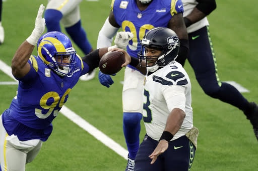 Seattle Seahawks quarterback Russell Wilson (3) throws under pressure from Los Angeles Rams defensive end Aaron Donald (99) during the second half of an NFL football game Sunday, Nov. 15, 2020, in Inglewood, Calif. (AP Photo/Jae C. Hong)