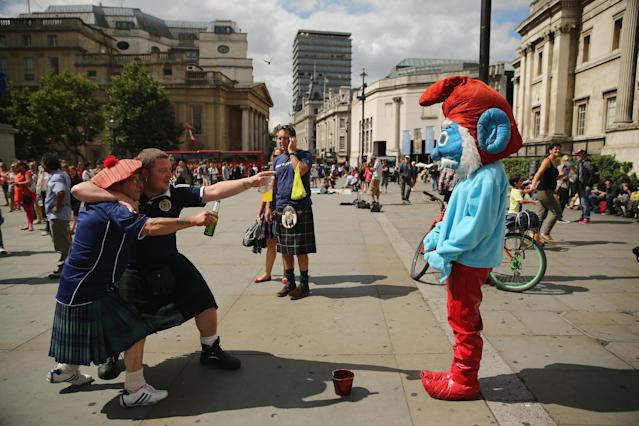 LONDON, ENGLAND - AUGUST 14: Two Scotland fans try to tempt a smirf to react in Trafalgar Square ahead of their international friendly match against England tonight on August 14, 2013 in London, England. Scotland and England will meet at Wembley stadium tonight for their first international in 14 years. (Photo by Dan Kitwood/Getty Images)